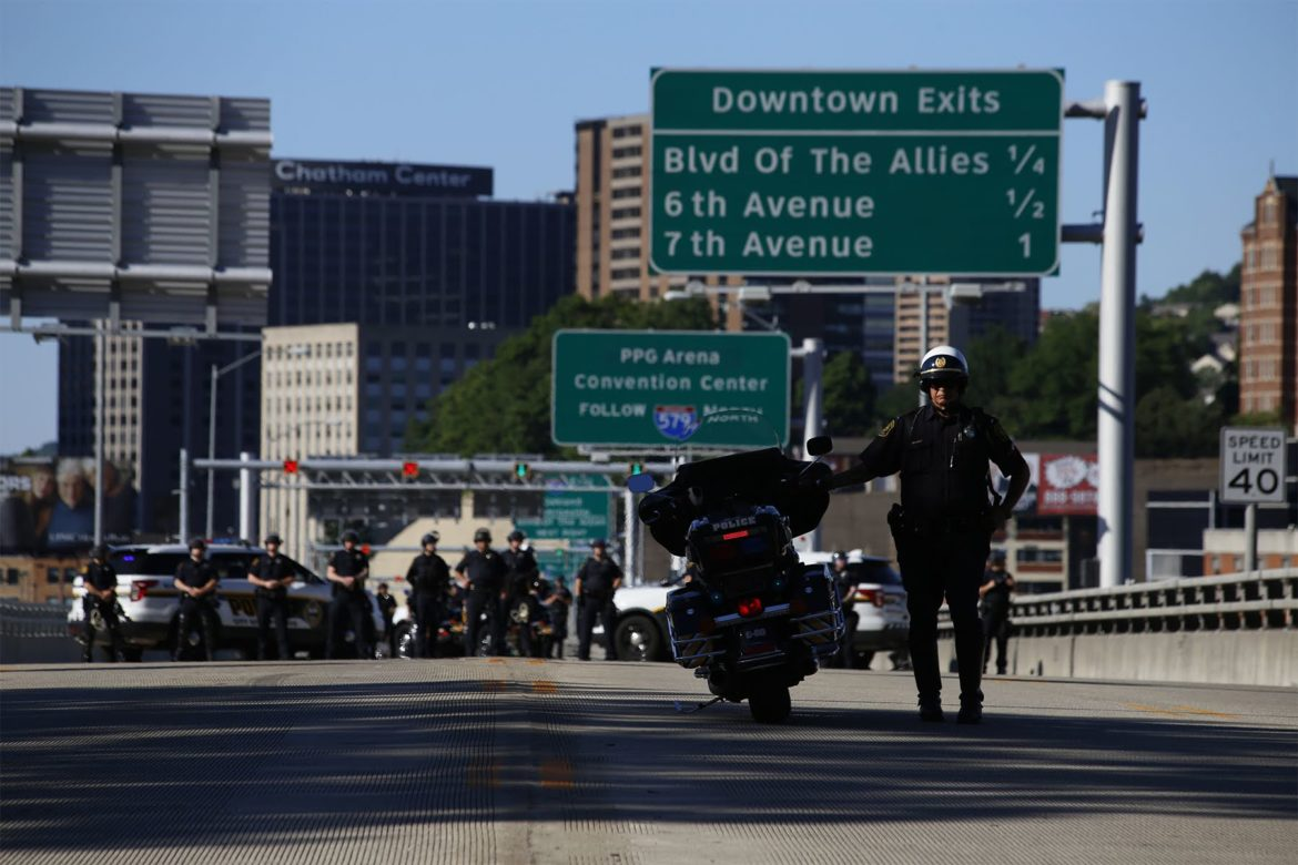 A police officer on the Liberty Bridge watches as protesters proceed down P.J. McArdle Roadway from Mount Washington en route to Downtown Pittsburgh on Sunday. (Photo by Ryan Loew/PublicSource)