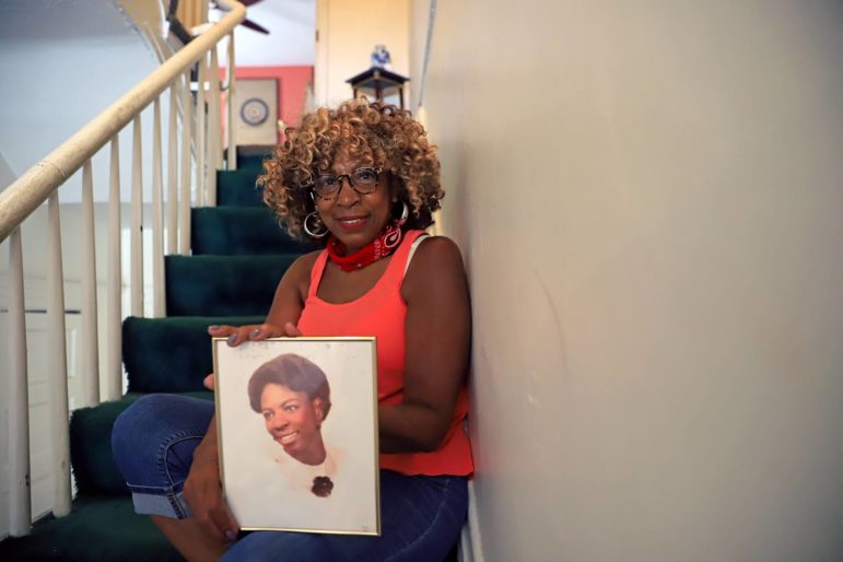 Brenda Tate is holding a photo of herself as a teenager in her home in the Hill District. (Photo by Jay Manning/PublicSource)