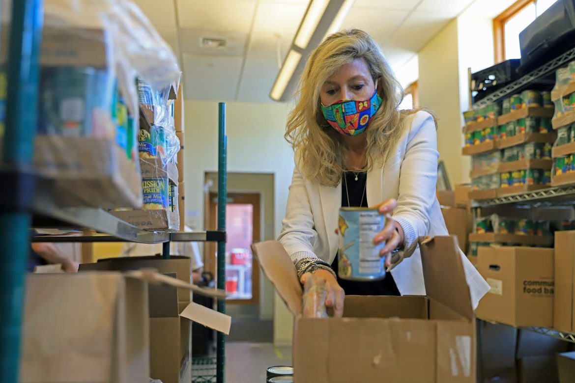 Carole Bailey, president and CEO of the East End Cooperative Ministry, prepares a box in the organization's food pantry. (Photo by Jay Manning/PublicSource)
