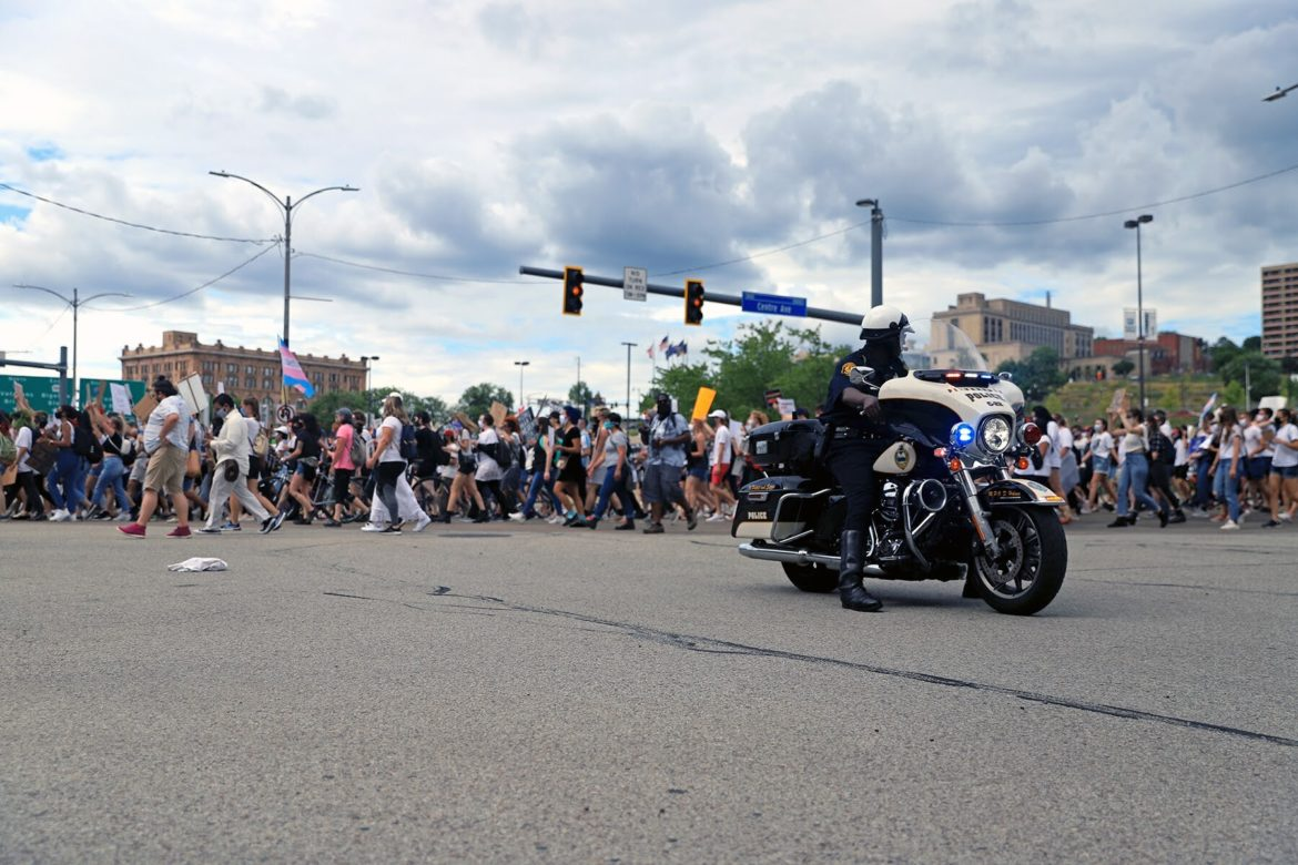 A police officer blocks traffic as people walk by chanting during a June 18, 2020 march against police violence from Freedom Corner. (Photo by Jay Manning/PublicSource)