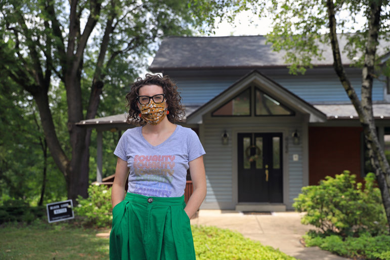 Photograph of Casey Swartz standing outside her house, wearing a face mask and looking straight at the camera.