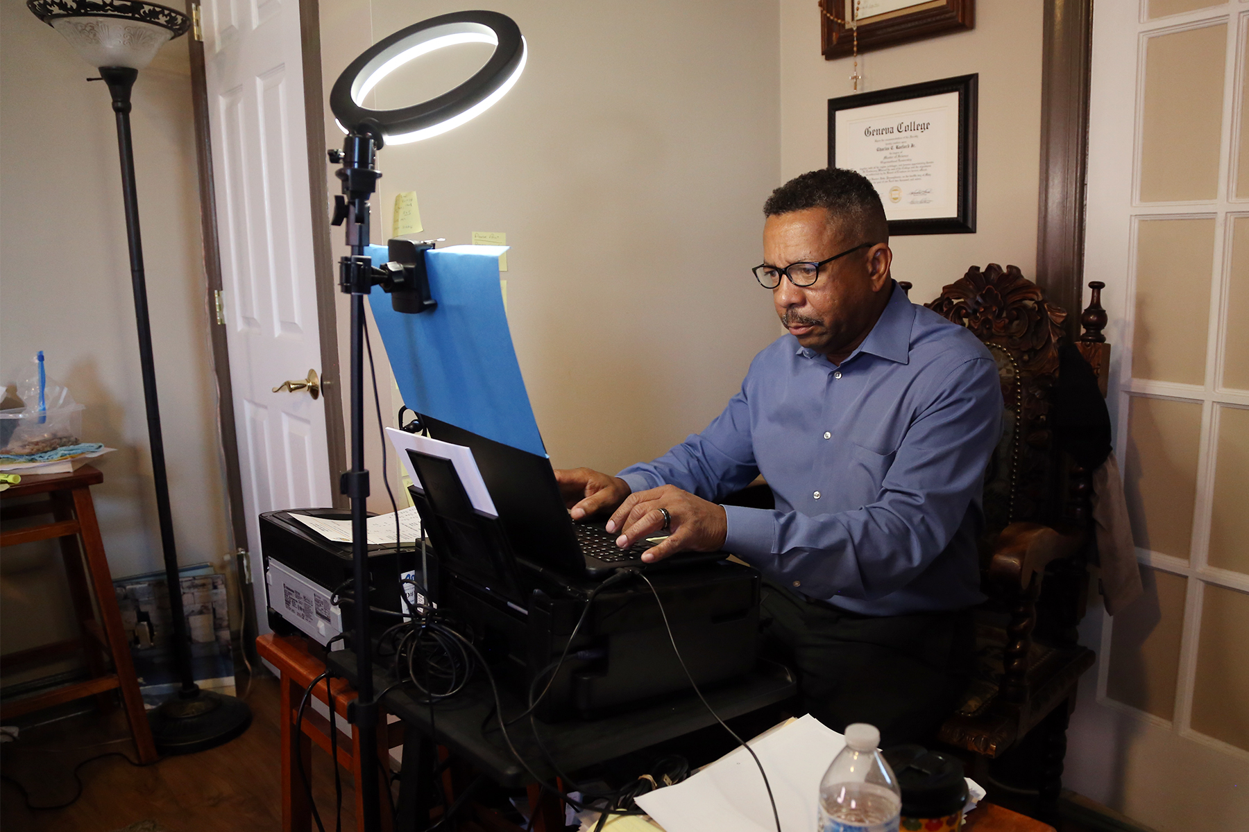 Jody Raeford sits at a desk with an overhead light, typing on a laptop computer.