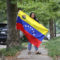 Mariana Benitez stands outside facing the camera and holding the flag of Venezuela, where she was born.