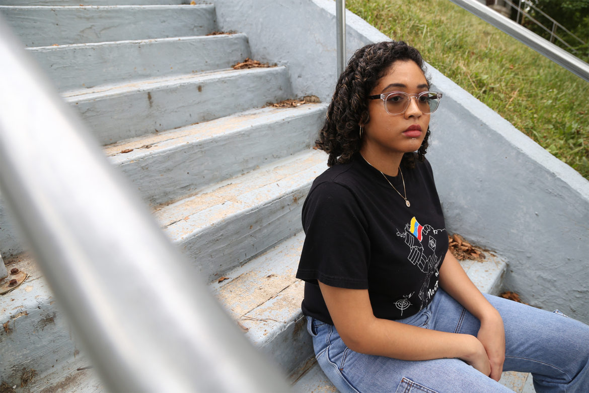 Mariana Benitez sits on steps outside, facing away from the camera.