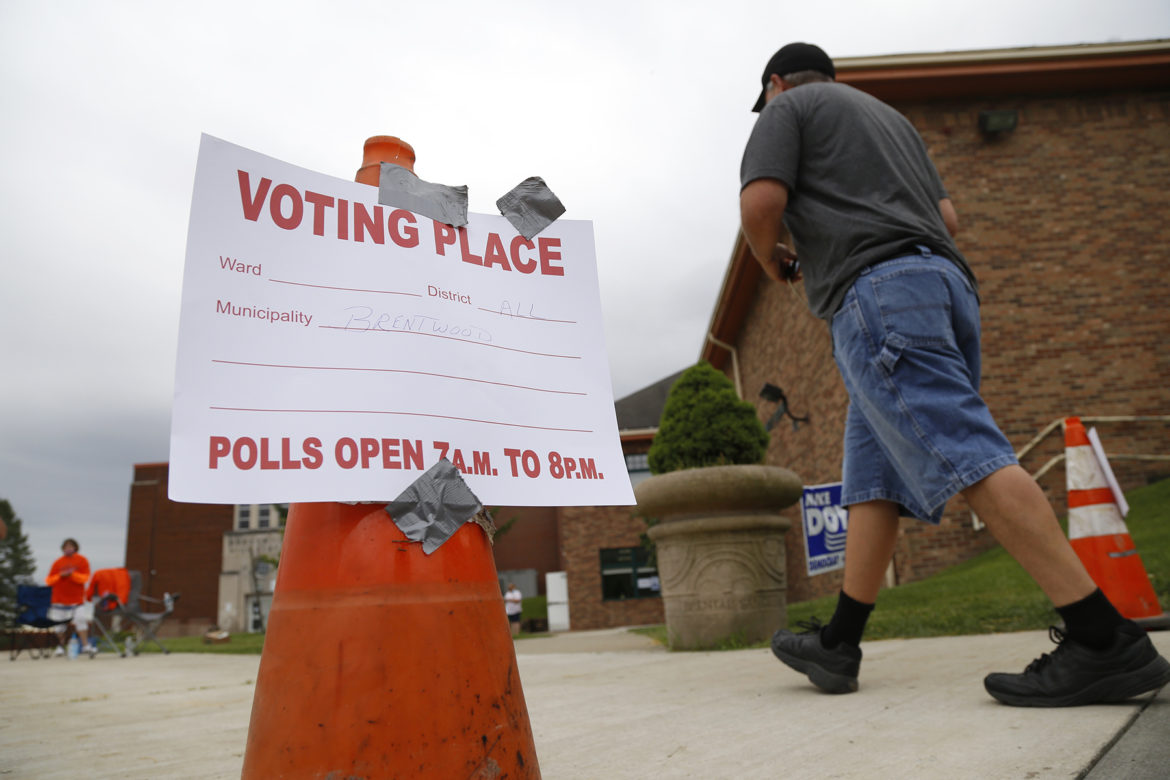 """A person walks past a sign taped to a traffic cone that reads, """"Voting place. Polls open 7 a.m. to 8 p.m."""""""
