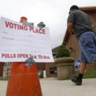 "A person walks past a sign taped to a traffic cone that reads, ""Voting place. Polls open 7 a.m. to 8 p.m."""