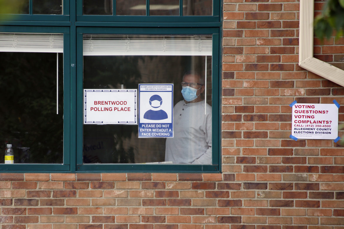 A person wearing a face mask looks out a window of the Brentwood Library. Signs attached to the window advise people entering to wear face coverings.