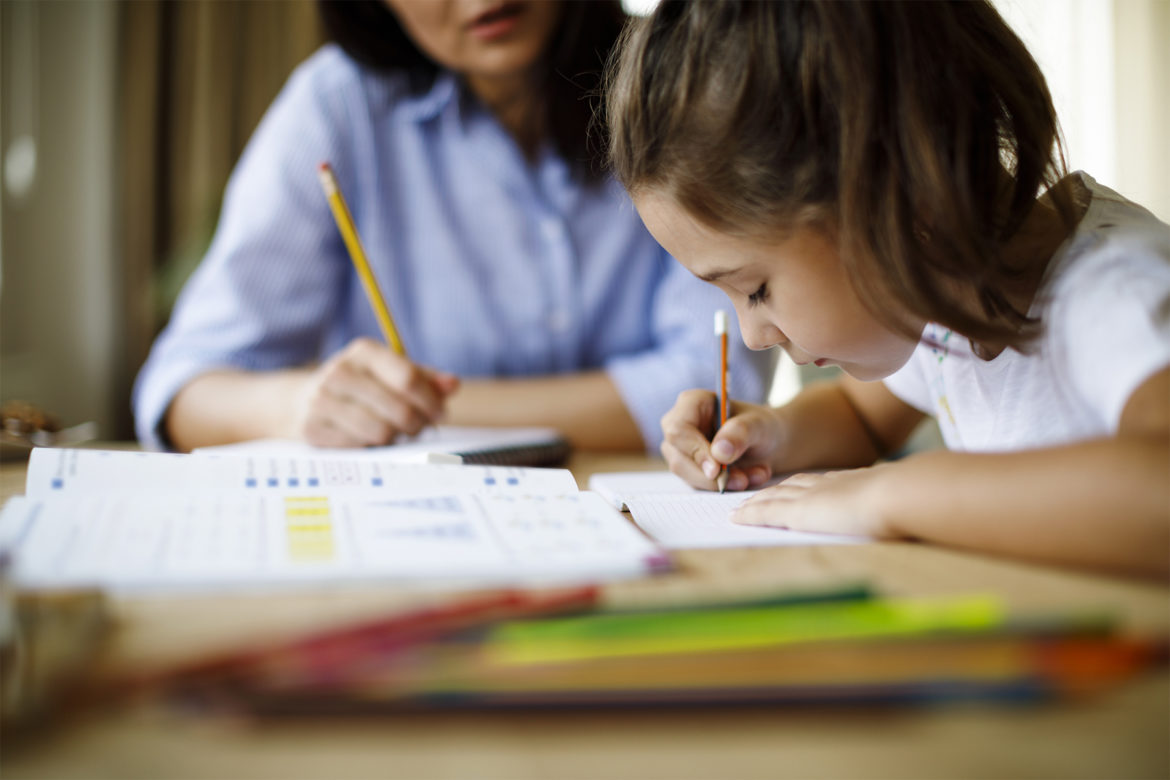 Mother helping child with schoolwork. (Photo via iStock)