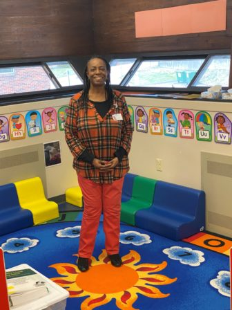 Willina Walker stands inside a room decorated with colorful posters depicting the letters of the alphabet.