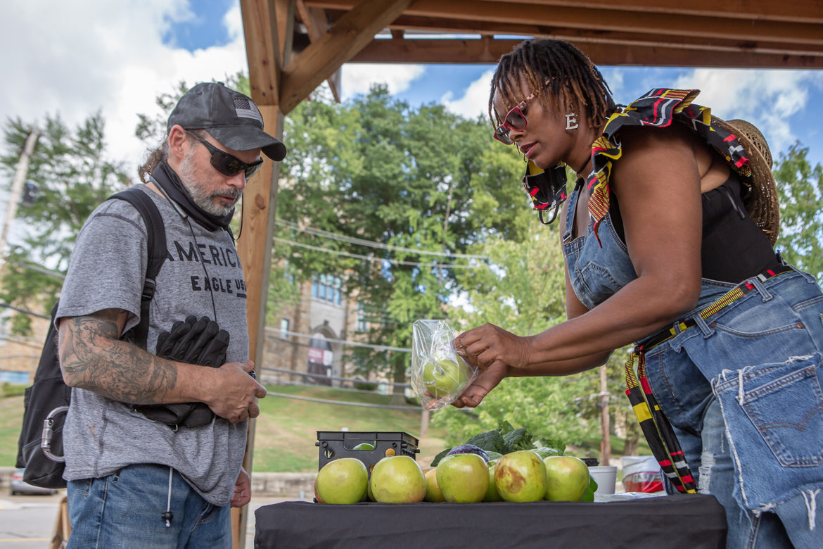 Ian Kriebel (left), an Army veteran and lover of fruit, purchased green apples from the weekly farmers market organized by Ebony Lunsford-Evans, owner of FarmerGirlEB in the West End. (Photo by Brian Cook)