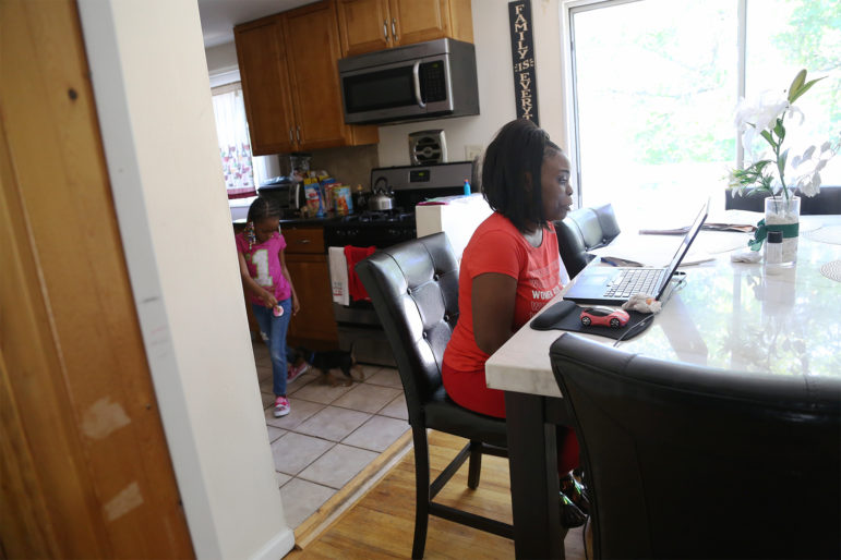 Leah McDougald sits in front of her computer at her kitchen table.