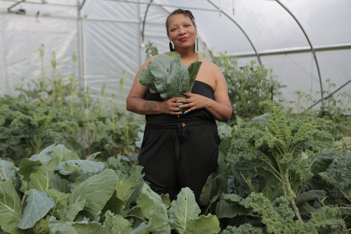 "Raqueeb Bey stands inside the Homewood Community Historic Farm's greenhouse, referred to as ""The Green Trap House."" (Photo by Brian Cook)"