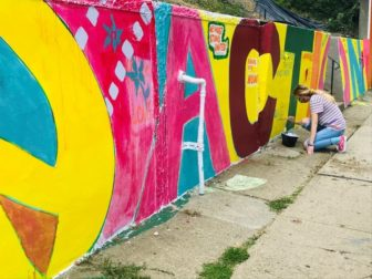 A woman kneels on the sidewalk painting a colorful mural.