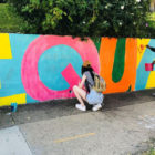 Three young people painting a mural in Oakland.