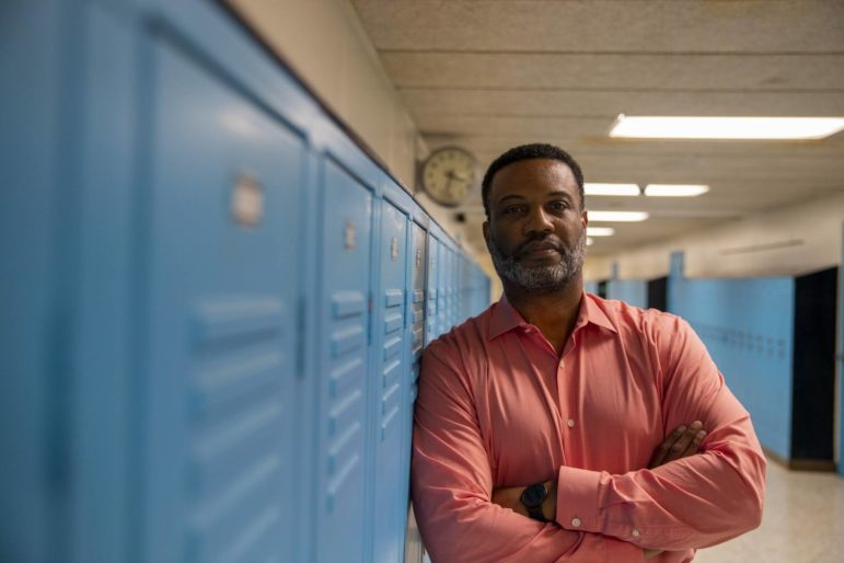 Superintendent James Harris of the Woodland Hills School District stands in front of a row of blue lockers.