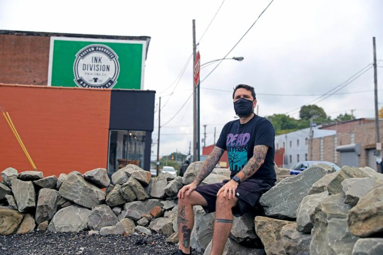 Jason Lott sits on rocks outside of his Braddock-based shirt printing business, Ink Division.