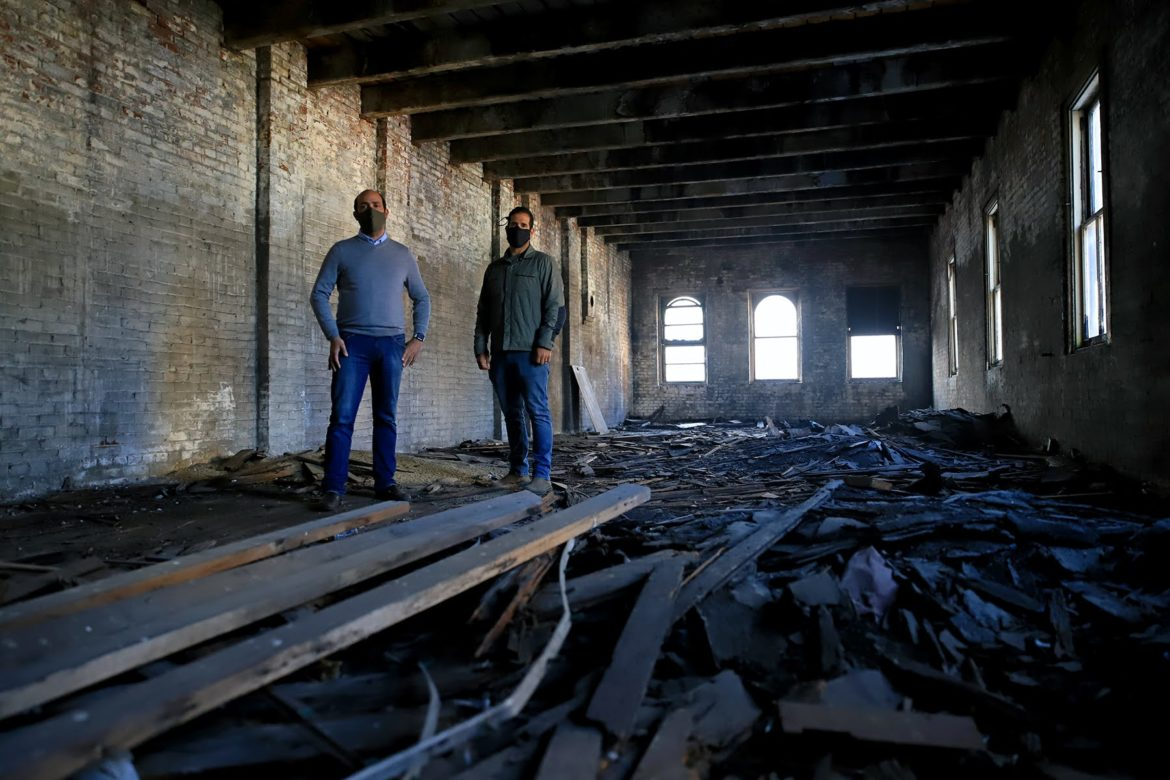 Brothers Michael (left) and Nicholas (right) Troiani in one of their buildings in Downtown Pittsburgh's Firstside district. They say deteriorating brick makes it impossible to save the structures. (Photo by Jay Manning/PublicSource)