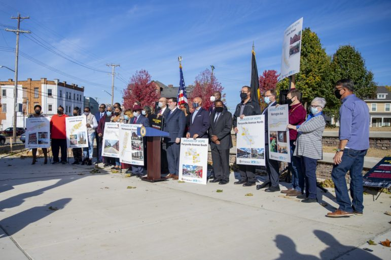 Political and neighborhood leaders gather behind maps of the seven neighborhood business districts that will be prioritized under the Avenues of Hope initiative, at a press conference in Larimer on Oct. 14, 2020. (Photo by Jay Manning/PublicSource)