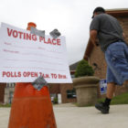 "A person walking in front of a sign that says ""Voting place."""