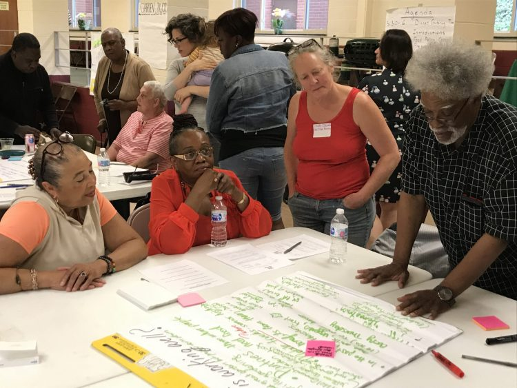 People gathered around a table during a Food Action Plan planning session.