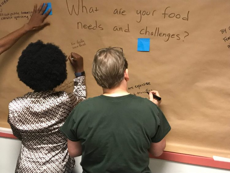 Two people writing answers on a board to a question about food security.