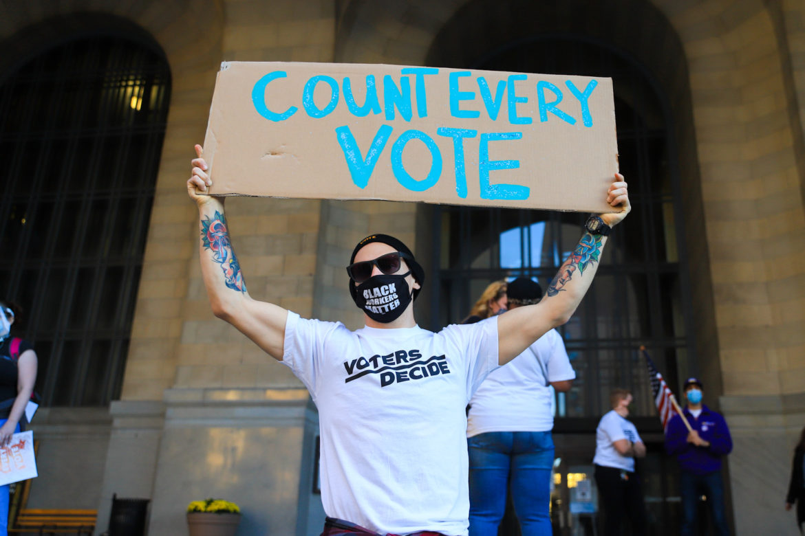 "David Gabig holds aloft a ""Count Every Vote"" sign at a Wednesday afternoon rally on the portico of the City-County Building, in Downtown Pittsburgh, on Nov. 4, 2020. (Photo by Jay Manning/PublicSource)"