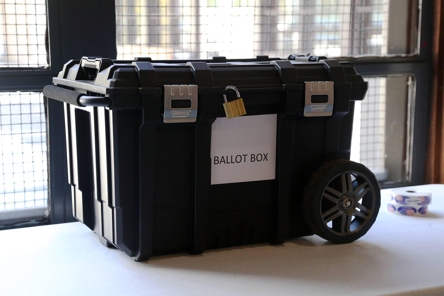 "A black plastic box with a lock on it and a sign that reads ""ballot box."""