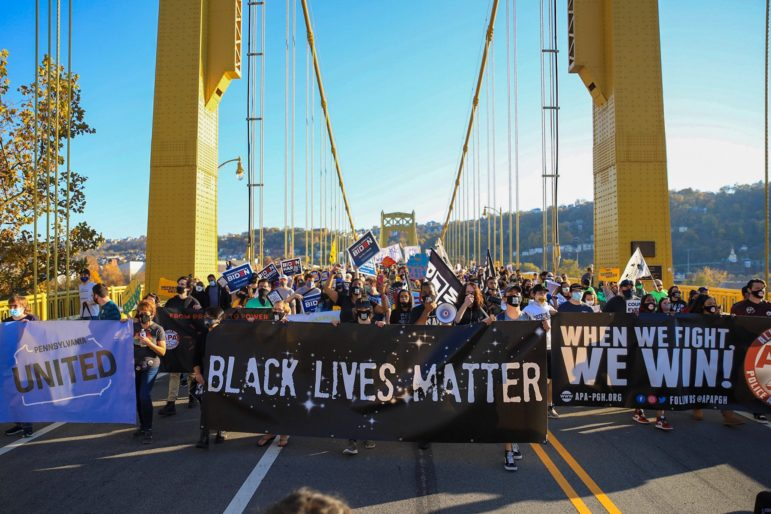 The rally marches across 10th St bridge towards the City-County building in downtown Pittsburgh, PA.