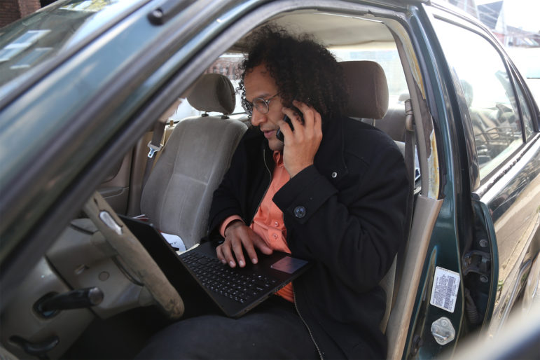 G.L. Johnson, field director for the Alliance for Police Accountability, talks on the phone while looking at canvassing data on Oct. 31 in Rankin. (Photo by Ryan Loew/PublicSource)