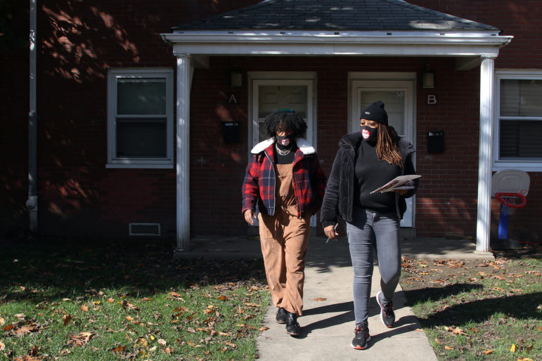 State Rep. Summer Lee, D-Swissvale, (left) and Brandi Fisher, president and CEO of the Alliance for Police Accountability, walk through Rankin's Hawkins Village on Oct. 31, knocking on doors and encouraging residents to vote. (Photo by Ryan Loew/PublicSource)