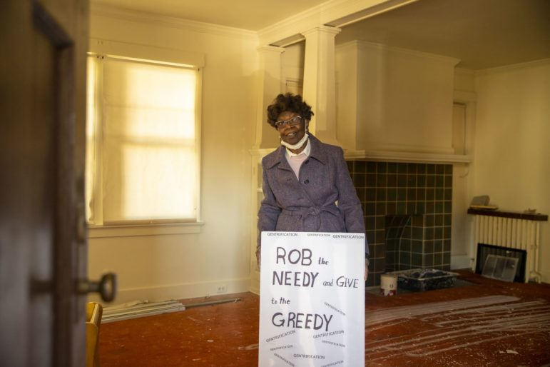 Kathleen Wilson stands within a four-unit house, owned by her family since 1983, on Wilkinsburg's Peebles Street. The sign was displayed outside of the house on Nov. 9, when attorney Marc Taiani and several inspectors arrived and scoured the property for information to be submitted in support of his company's petition to take control of the house under the state's conservatorship law. (Photo by Jay Manning/PublicSource)