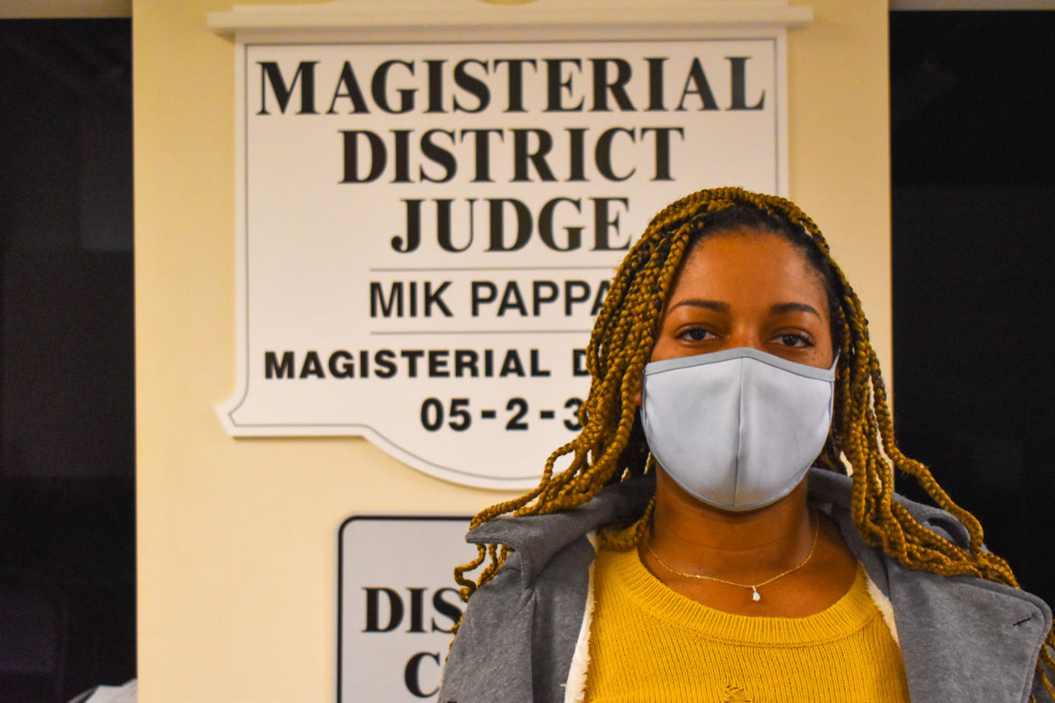 """Diona Brown wears a mask while standing in front of a sign that says """"Magisterial District Judge Mik Pappas."""""""