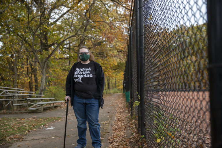Cori Frazer, the executive director of the Pittsburgh Center for Autistic Advocacy, and a member of the City-County Task Force on Disabilities, stands near a tennis court fence in Frick Park (Photo by Jay Manning/PublicSource)