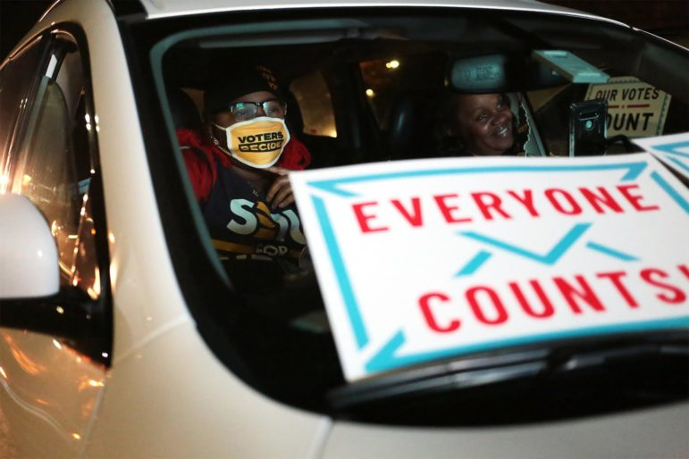 Ronelle Burton (right) and her daughter Nekia Burton, a downtown cleaner and SEIU 32BJ member, watch election results at a drive-in election night event in Point Breeze North. (Photo by Ryan Loew/PublicSource)