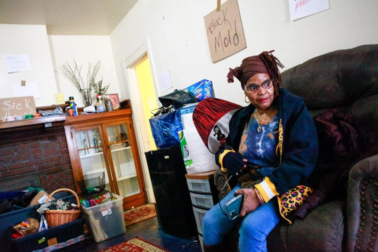 Linda Robinson holding a lamp during her move from a rental home in early 2020. Robinson was in the midst of a dispute with her landlord and alleged that she had found black mold in the home. (Photo by Kimberly Rowen/PublicSource)