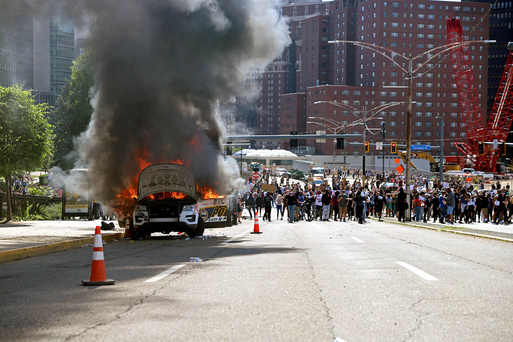 A police car burning on a Pittsburgh street amid a protest.