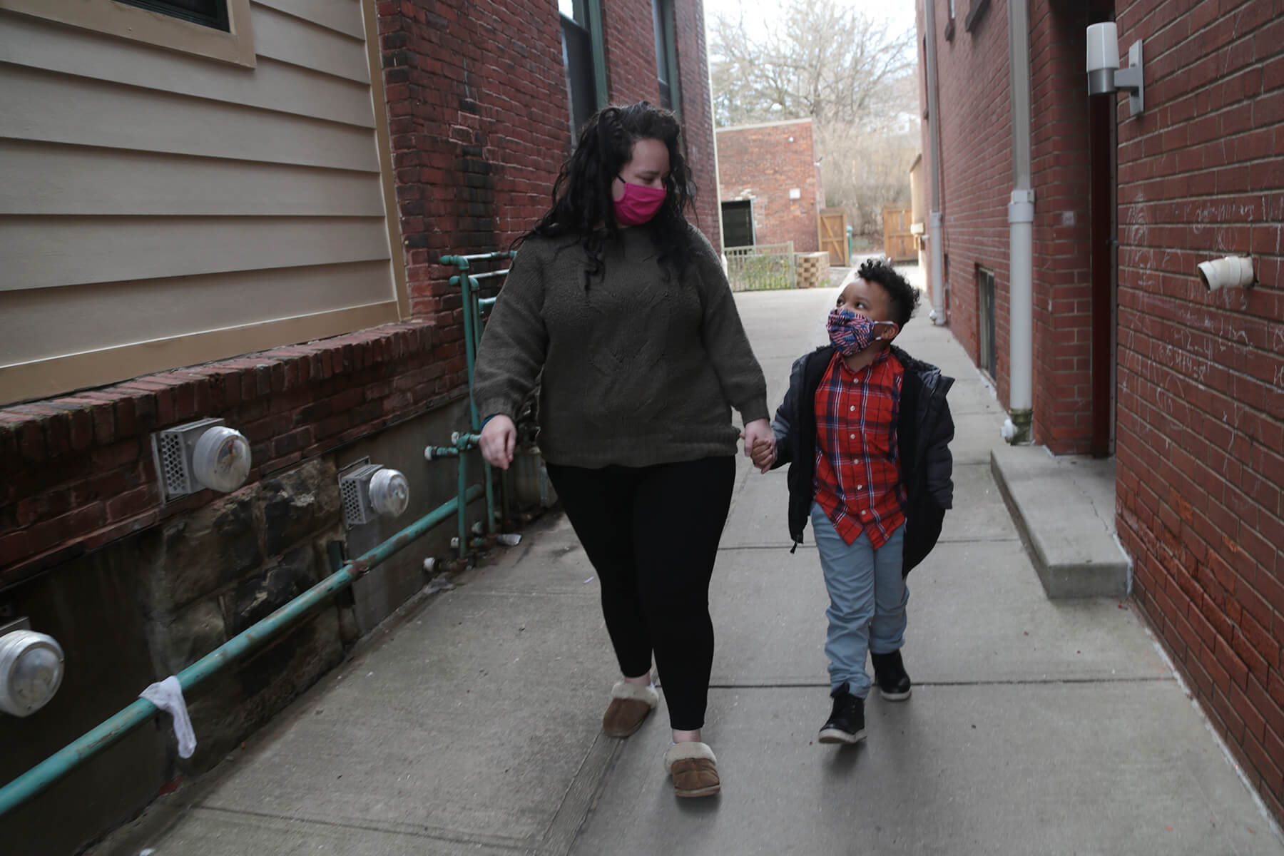 """Amber J. walks outside with her 5-year-old son Laron. """"My mom always said if you do the right thing, God will bless you,"""" she said. """"And it's finally looking up."""" (Photo by Ryan Loew/PublicSource)"""