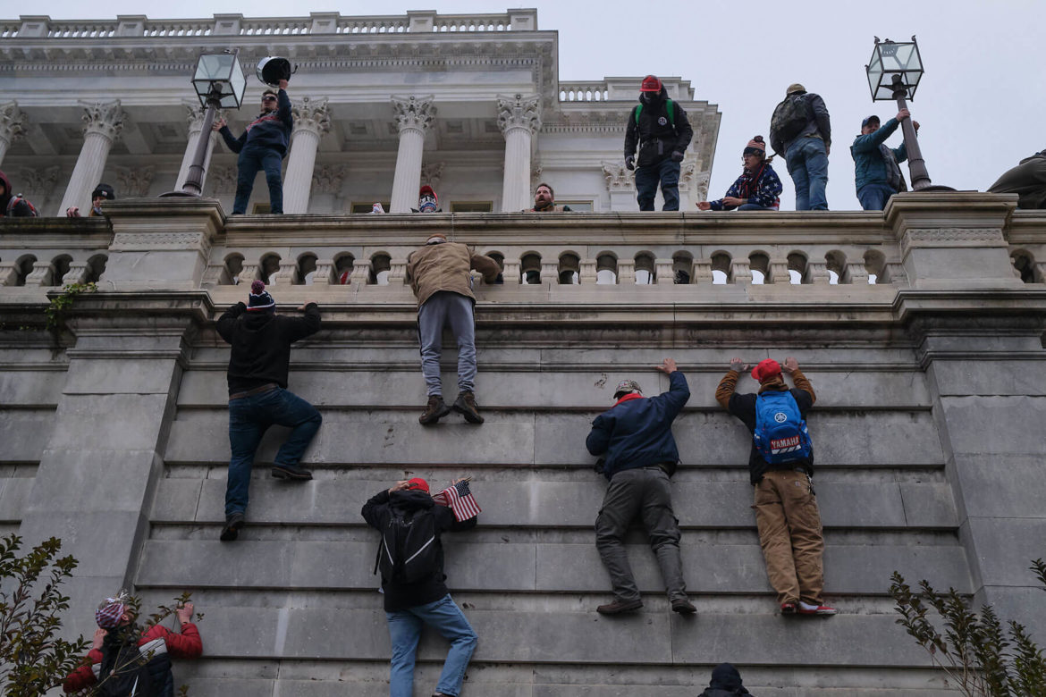 Insurrectionists scale the walls of the Capitol Building from the West Front. (Quinn Glabicki for PublicSource)