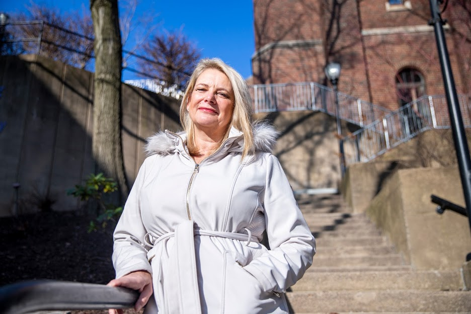 Susan O'Rourke leans against a handrail on Carlow University's campus in front of a concrete staircase and a red brick building. She has blonde hair and is wearing a white winter coat.