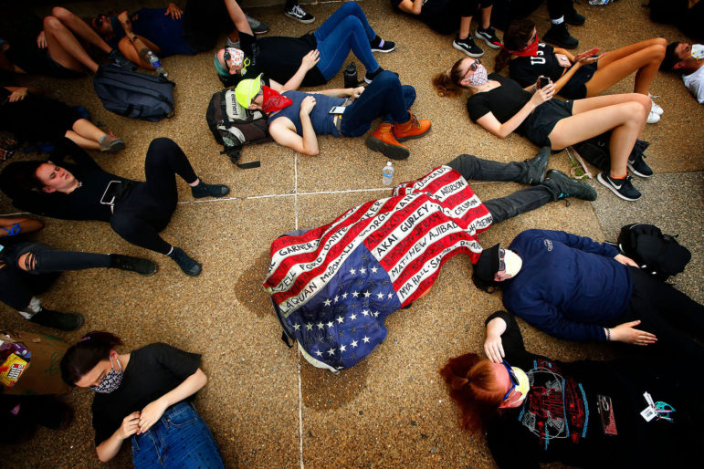 A protester lies underneath an American flag, covered in the handwritten names of Black people whose lives were lost at the hands of police, outside of the Allegheny County Jail during a Black Lives Matter protest on June 4, 2020. (Photo by Jared Wickerham/Pittsburgh City Paper)