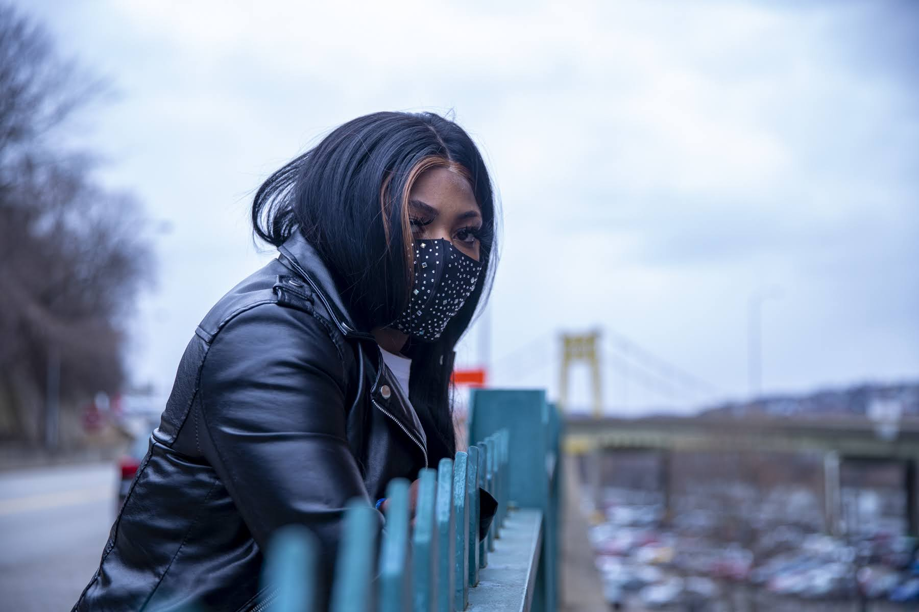 A woman in a black jacket and black face mask with rhinestones leans against a green railing in front of the Allegheny County Jail. A yellow bridge can be seen in the background.