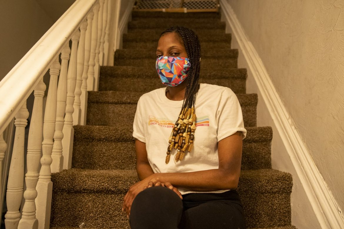 Ebony Long, 35, of Perry North sits on the staircase of the rental house from which her landlord is trying to evict her. (Photo by Jay Manning/PublicSource)