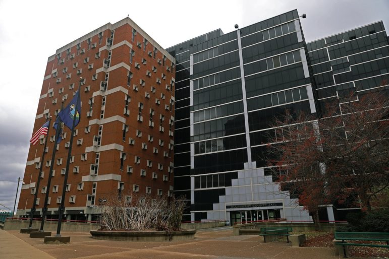 The front facade of Allegheny County Jail. The building is constructed of long, rectangular glass panels in the center and red brick on the left side.