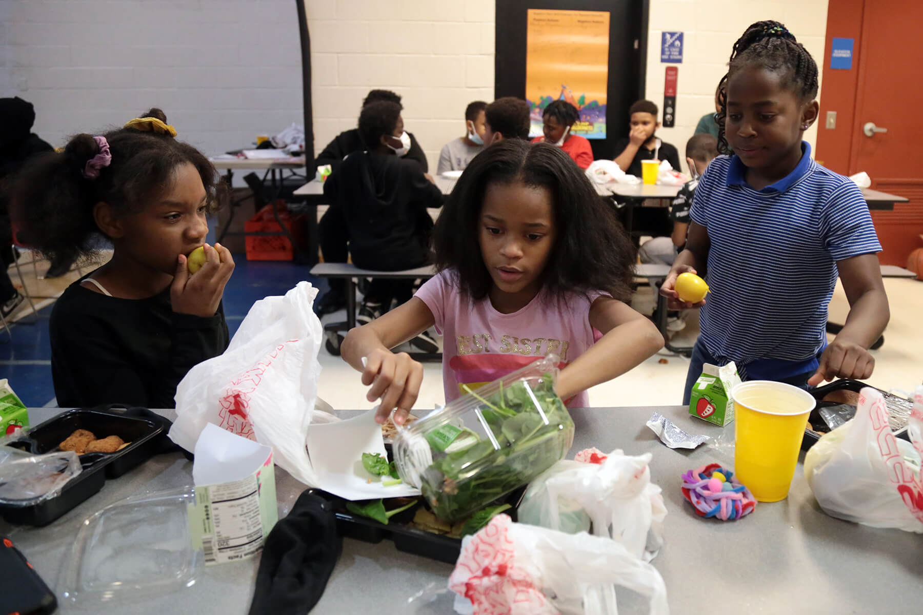 Essence Hamlin, 9, Leighton Staples, 8, and Demi Pirl, 7, (left to right) eat dinner at the Boys & Girls Clubs of Western Pennsylvania Duquesne clubhouse on March 11. (Photo by Ryan Loew/PublicSource)