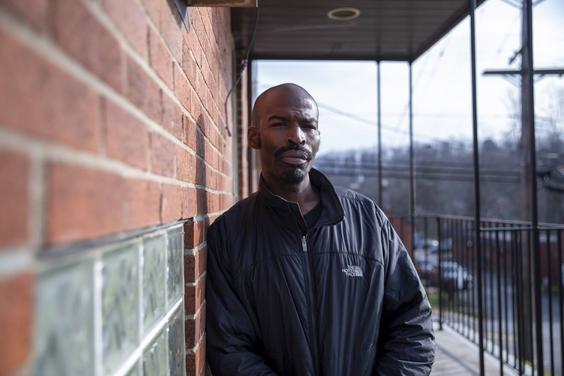 dajuan davis leaning against a brick wall outside of his house