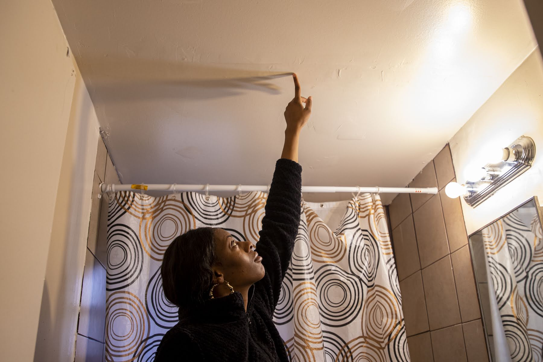 Shanese Nelson pointing to water damage in the bathroom.