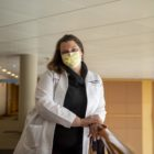 Dr. Jamie Wright leans over a metal railing inside UPMC Magee-Womens Hospital. She is wearing a white coat, black sweater and yellow face mask. The wall behind her is yellow.