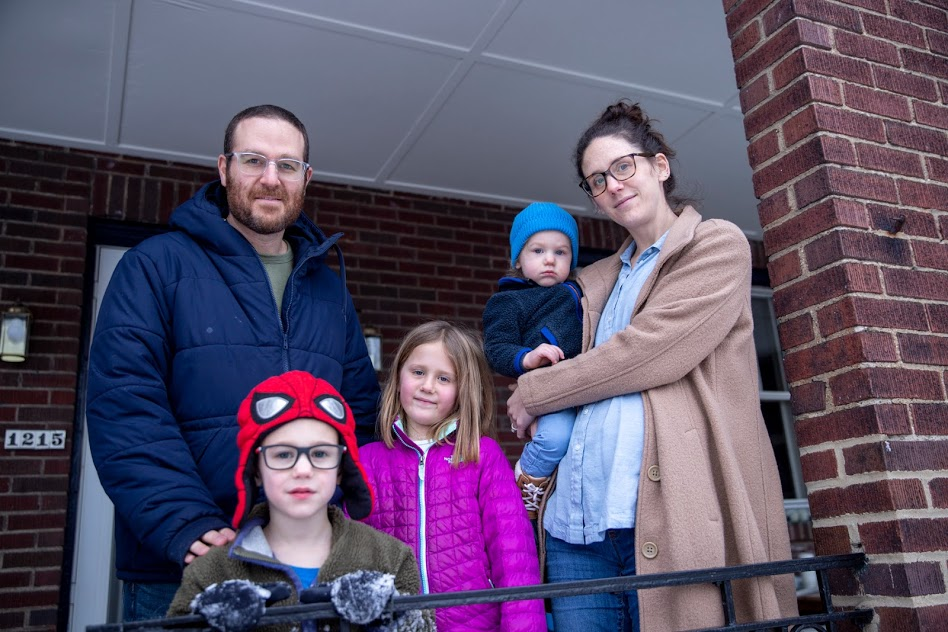 Laurie Sloan, a white woman with brown hair and glasses, stands with her husband and three children on the porch of their house. The porch is dark brown brick. In front of them is a black metal porch railing.