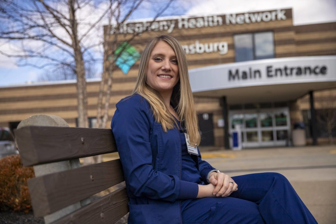 Courtney Acampora sits on a bench outside the main entrace to Canonsburg hospital, Allegheny Health Network