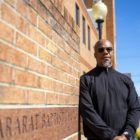Rev. Curtis stands against a wall outside Mount Ararat Baptist Church